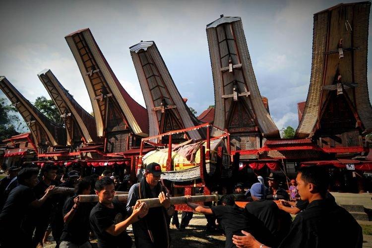Sejumlah kerabat mengarak patung dan jenasah saat prosesi ma'palao di Sa'dan, Rantepao, Toraja Utara, Senin (22/12). MaÕPalao merupakan bagian dari prosesi upacara rambu solo yakni proses perarakan jasad dari area Rumah Tongkonan ke tempat pemakaman atau patani. ANTARA FOTO/Zabur Karuru/ed/pd/14