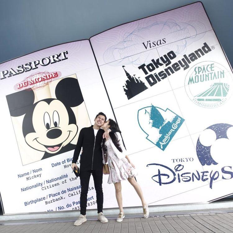 Berpose romantis berlatar Mickey Mouse.