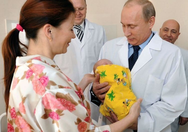 Russian Prime Minister Vladimir Putin, right, takes newborn baby Pyotr Nikolayev from his mother Yelena in a maternity hospital in Kaliningrad, Russia, Wednesday, Nov. 2, 2011. Baby boy Pyotr Nikolayev was born in the western Russian city of Kaliningrad on Monday, the day when the United Nations said a symbolic 7 billionth baby was born. (AP Photo/RIA Novosti, Alexei Nikolsky, Pool)
