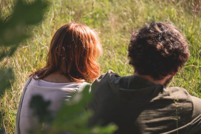 people-photography-of-man-and-woman-sitting-on-green-grass-field