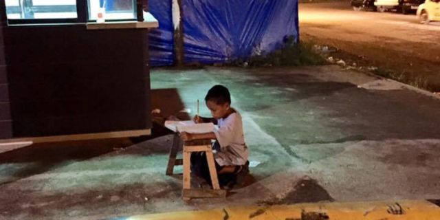 boy studying on street