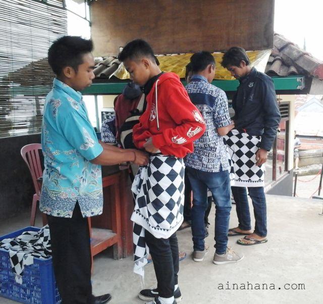 Pemakaian kain Saput Poleng sebelum masuk ke area candi