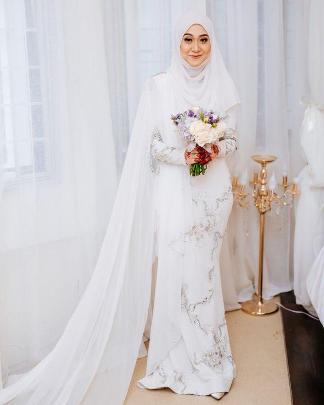 7ac0ebef6d7 Sang pengantin wanita dalam busana terusan mermaid yang berhiaskan kristal  berkilauan untuk menghadiri akad nikah. Kain yang menjulang panjang dari  bahunya ...